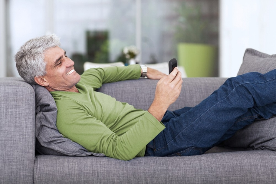 middle aged man reading text message on mobile phone while lying on couch